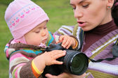 Mother holds baby with camera — Stock Photo