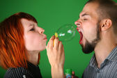 Girl with red hair blows soap bubble in mouth to guy — Stock Photo