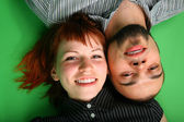 Girl with red hair and guy lie head to head — Stock Photo