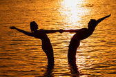 Pair keeps for hands in sea on sunset — Stock Photo