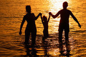 Parents with child in sea on sunset — Stok fotoğraf