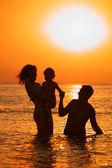 Padres con el niño en el mar en sunset — Foto de Stock
