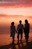 Three on shore seas in waves on sunset — Stock Photo