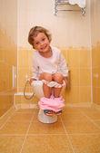 Little girl is sitting on toilet — Stock Photo
