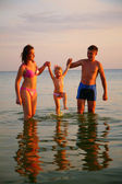 Parents hold daughter from hands in sea — Stock Photo