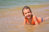 Little girl lies in waves on shore — Stock Photo