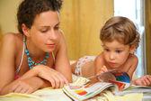 Mor och barn läsa tidningen — Stockfoto