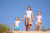 Mother and children on sand — Stock Photo