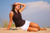 Young beuty woman sit on sand — Stock Photo