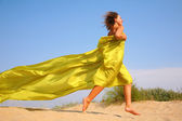 Young girl runs on sand in yellow shawl — Stock Photo