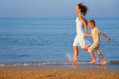 Madre con figlio in esecuzione sul bordo del mare — Foto Stock