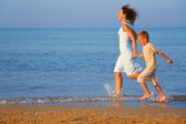 Mother with son running on edge of sea — Stock Photo