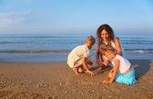 Madre juega con niños en la arena al borde del mar — Foto de Stock