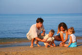 Parents play with children on sand at edge of sea — Stock Photo