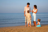 Parents with children standing at edge of sea — Stock Photo
