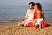 родители с ребенком, сидя на песке на берегу моря — Стоковое фото