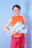 Young woman with rolls of wall-paper — Stockfoto