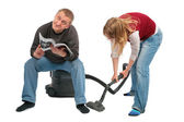 Woman vacuums, man sits on vacuum cleaner with magazine — Stock Photo
