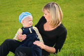 Mother and child sit on meadow — Stock Photo