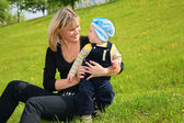 Mother with baby sit on grass — Stock Photo
