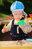 Küçük çocuk kum havuzunda çalış — Stok fotoğraf