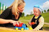 Mother plays with child with toy car — Stock Photo