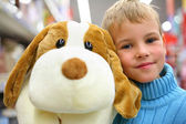 Boy with toy dog in shop — Stock Photo