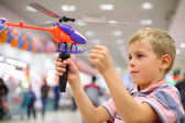 Boy in shop with toy helicopter — Stock Photo