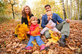 Family with yellow maple leaves in wood in autumn — Stok fotoğraf