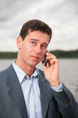 Portrait of man near pond, which speaks on cell phone — Stock Photo