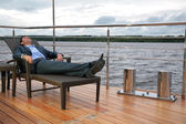 Portrait of man, who rests in chaise lounge on wharf near water — Stock Photo