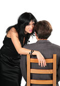 Beautiful brunette in black dress whispers on ear man sitting on chair — Stock Photo
