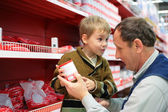 Grandfather and grandson choose conserve in food shop — Stock Photo