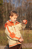 Boy in autumn wood with rope in hands — Stock Photo