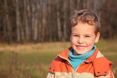 Boy in autumn wood — Stock Photo