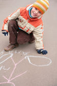 Boy drawing by chalk on asphalt — Stock Photo
