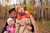 Grandfather with grandsons in forest in autumn look up — Stock Photo