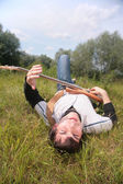 Young man lies with guitar on grass — Stock fotografie