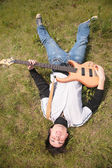 Young man lies with guitar on grass — Stok fotoğraf