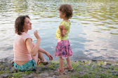 Mother with daughter near water — Stock Photo