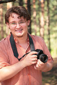 Photographer with camera in wood — Stock Photo