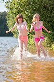 Two girl runs on water — Stock Photo