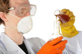 View on scientist in respirator and rubber gloves pours brown l — Stock Photo