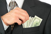 Dollars in pocket of coat and hand — Stock Photo