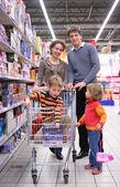 Rodziny z synem w koszyk w sklepie — Zdjęcie stockowe