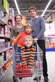 Family with children in cart in shop — Stock Photo
