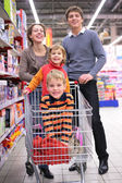 Ebeveynler çocukları alışveriş sepeti ile — Stok fotoğraf