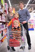 父母与孩子在商店里的购物车中 — 图库照片