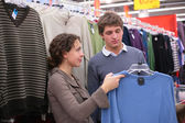 Pair chooses sweater in shop — Stock Photo
