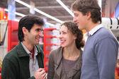 Three friends talk in shop — Stock Photo